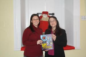 Natasha Bozek, Executive Director of the Literacy Coalition of New Brunswick, giving Ruth Murgatroyd, Executive Director of the York Sunbury Historical Society books that will be used in upcoming children programs.